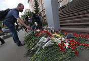 People bring flowers at the VGTRK building to pay tribute to journalist Igor Kornelyuk and sound engineer Anton Voloshin who were killed in a mortar attack near the city of Lugansk, eastern Ukraine on June 17, 2014