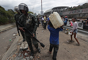 Members of the National Bolivarian Guard try disperse people trying to collect water in Caracas