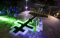 Russian Orthodox priest conducts a service on Epiphany at a hole in the form of Orthodox Cross at a pond in Tyarlevo village outside St.Petersburg, Russia
