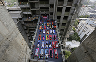 Indians performs yoga on a walk-way between two towers of an under construction high rise residential building as they mark International Yoga Day in Ahmadabad, India