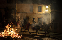 People ride their horses past a bonfire as part of a ritual in honor of Saint Anthony the Abbot, the patron saint of domestic animals, in San Bartolome de Pinares, Spain