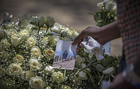 A family member puts a photo on flowers at the scene where the Ethiopian Airlines Boeing 737 Max 8 plane crashed shortly after takeoff on March 10 killing all 157 on board, near Bishoftu, south of Addis Ababa, Ethiopia