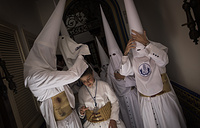 """Hooded penitents from """"La Candelaria"""" brotherhood preparing inside their house before taking part in a procession in Seville, Spain"""