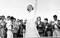 Actress Ingrid Bergman is snapped from all sides by a crowd of photographers at Cannes, 1956
