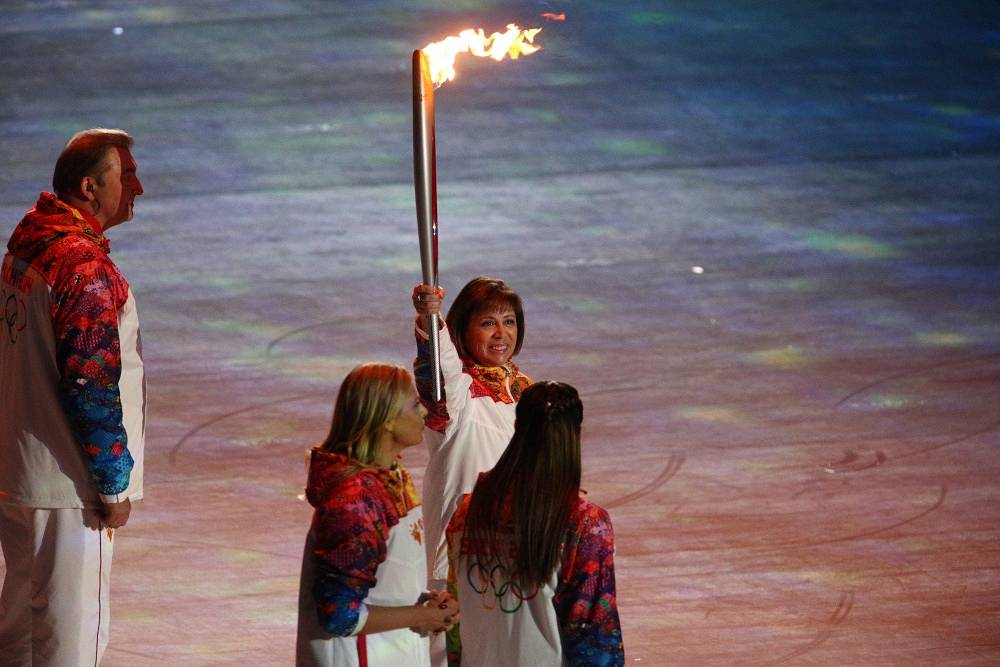 Irina Rodnina with the Olympic flame during the opening ceremony
