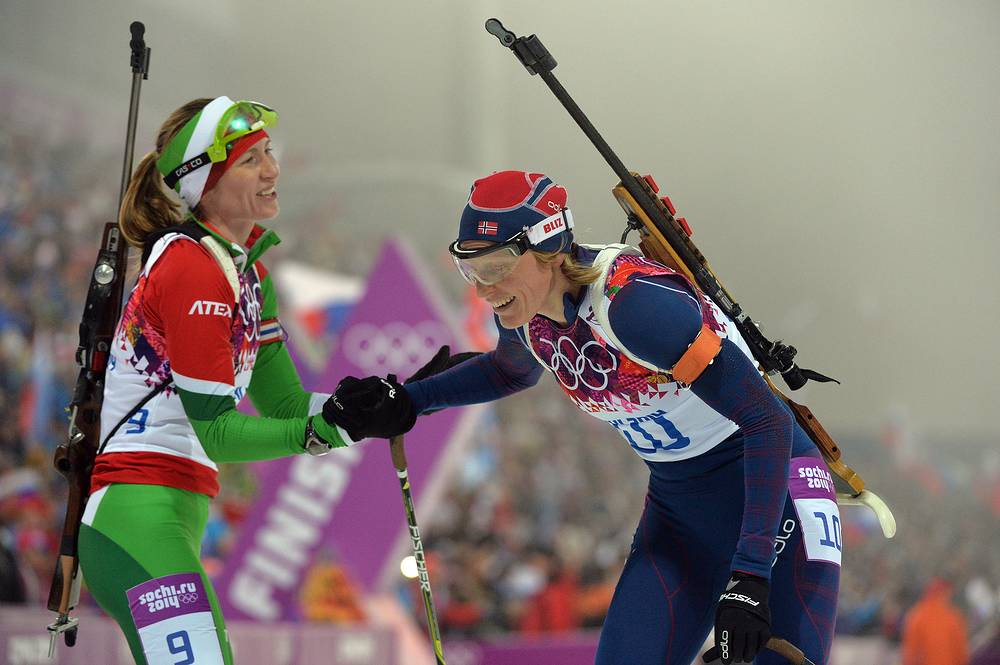 Darya Domracheva with Norway's Tora Berger, who won silver in women's 10km pursuit