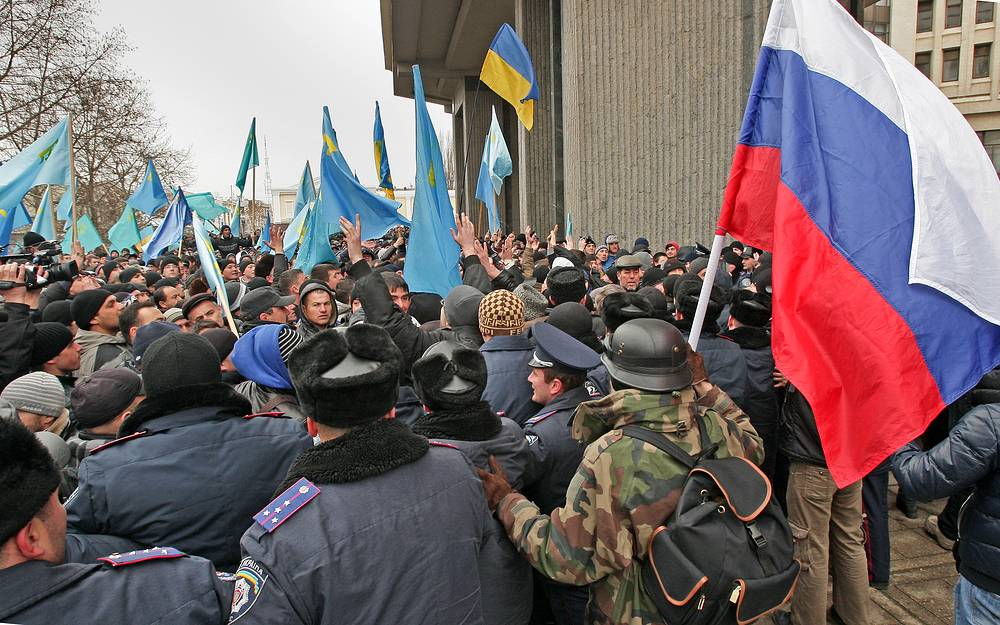 A man (R) holds a single Russian flag while Crimean Tatar activists wave their flags and shout slogans such as 'Crimea is not Russia, Glory to Ukraine'