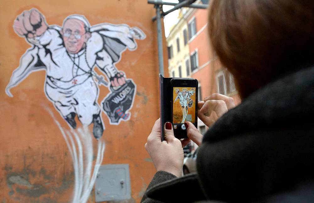A mural showing Pope Francis as Superman, flying through the air with his white papal cloak billowing out behind him and holding a bag bearing the word 'Values', in downtown Rome