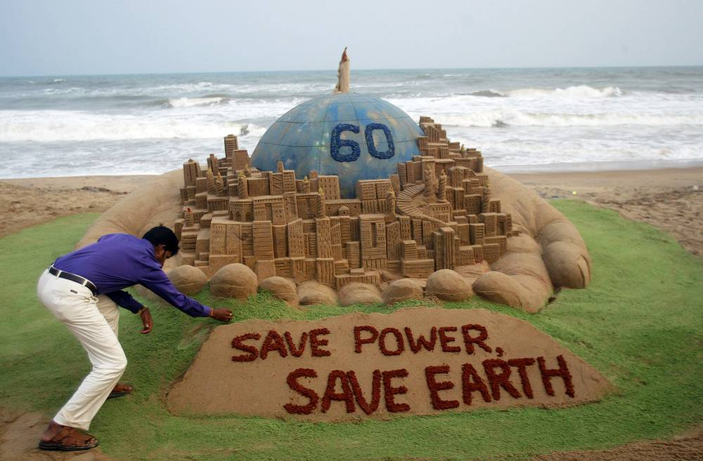 Sand artist gives finishing touches to the 'Save Earth and Save Power' sand sculpture, 2010