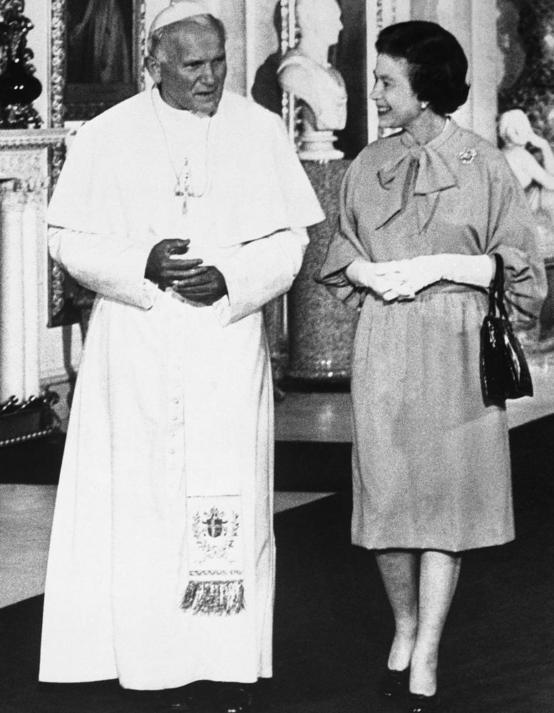 Pope John Paul II walks with Britain's Queen Elizabeth II through the Marble Hall at Buckingham Palace in London after their private audience