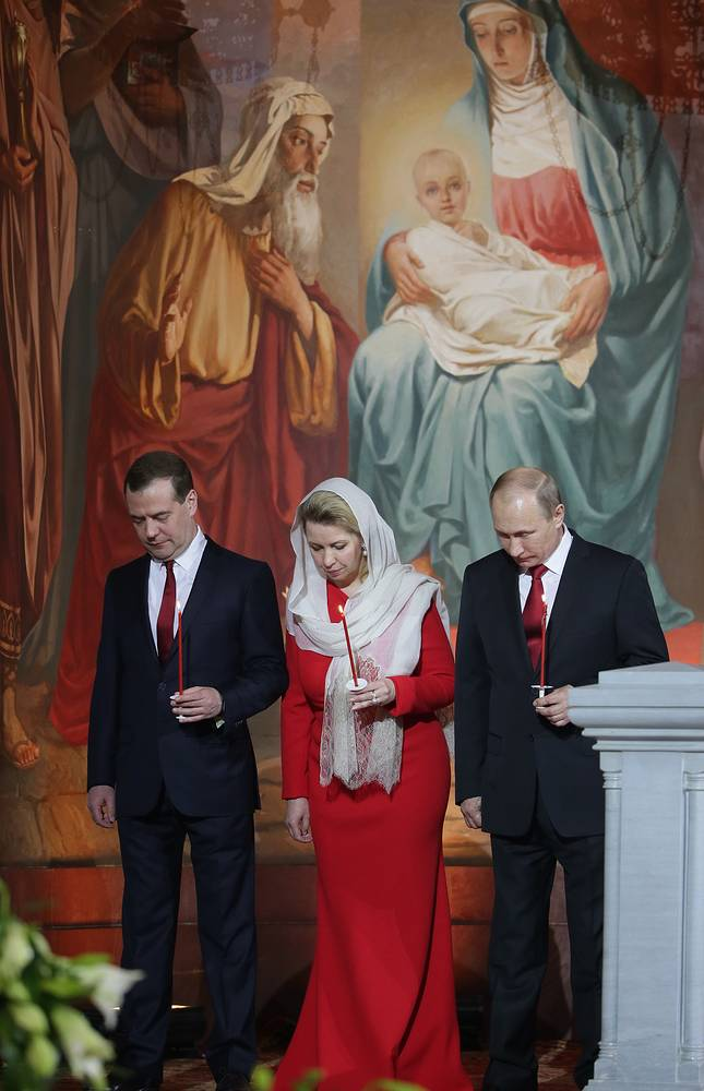 Russian President Vladimir Putin (right) and Prime Minister Dmitry Medvedev (left) with his wife (center)