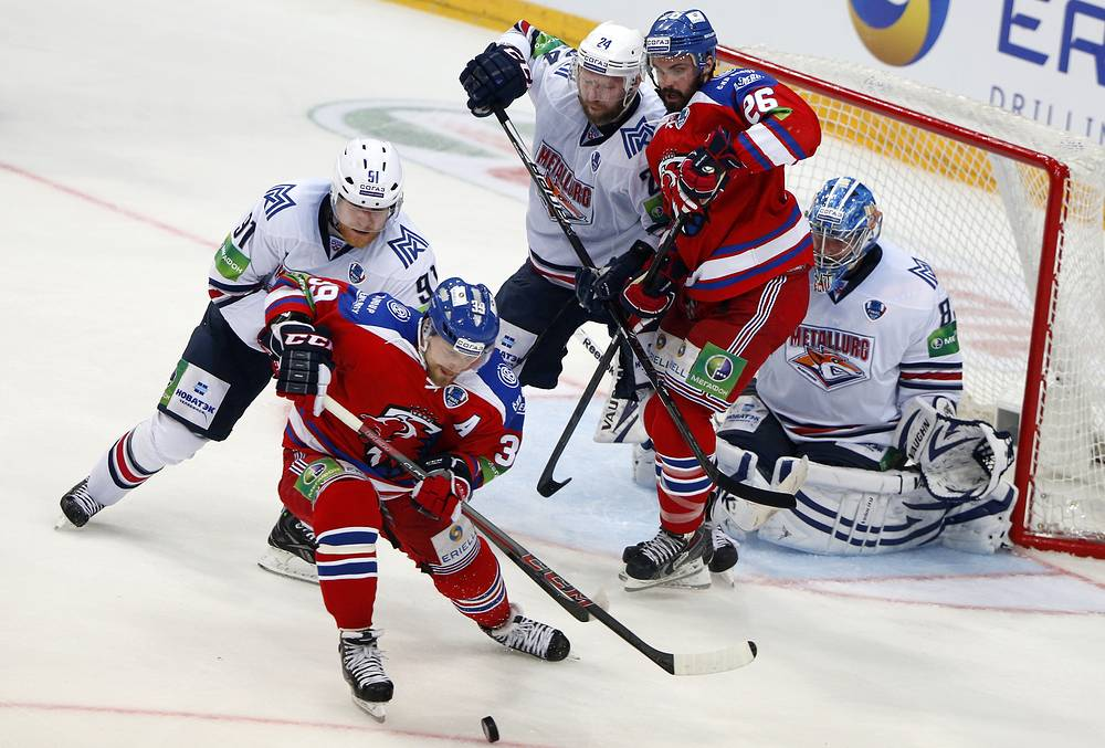 Metallurg's Mikhail Yunkov, Vladimri Malenkikh, goalie Vasily Koshechkin (L-R white) defend against Lev's Niko Kapanen, Michal Repik (L-R red)