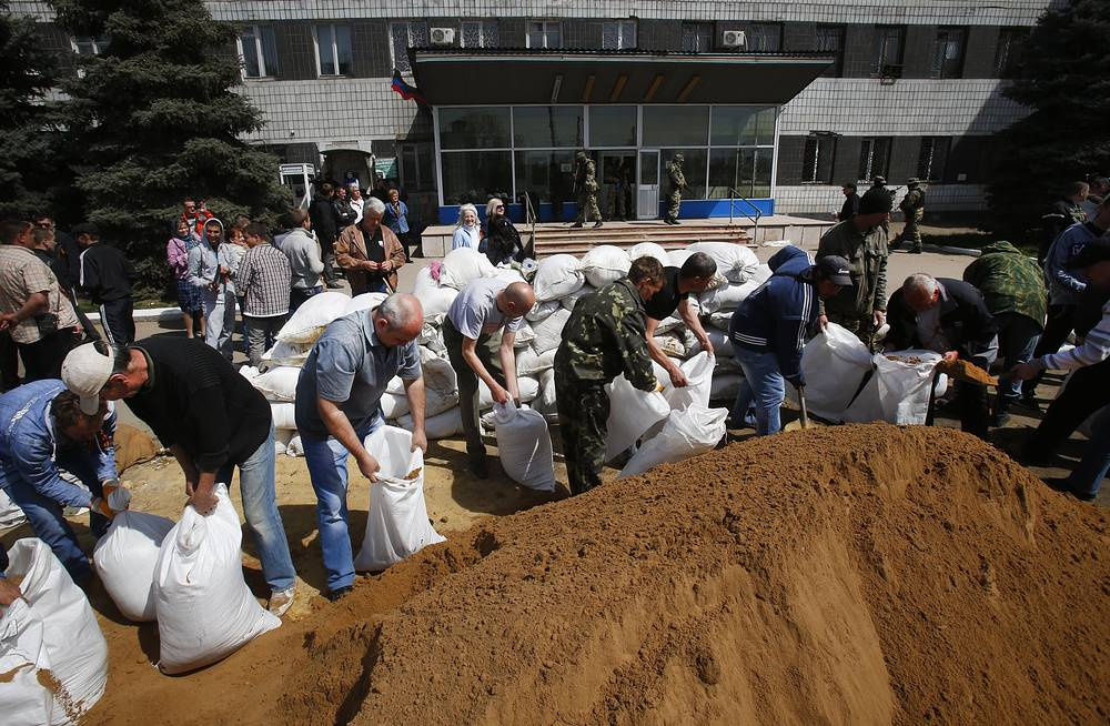 Local residents fill sandbags to form a barricade at the city hall in Kostiantynivka