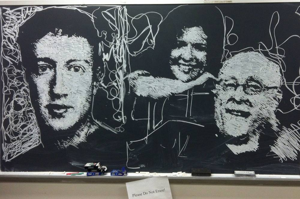 Mark Zuckerberg, Kara Swisher and Walt Mossberg depicted on a blcakboard at New York University