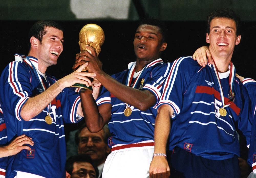 World Cup 1998 took place in France. In the final, the host played with Brazil and won 3-0. Photo: France soccer team stars Zinedine Zidane, Marcel Desailly and Laurent Blanc celebrate with the cup