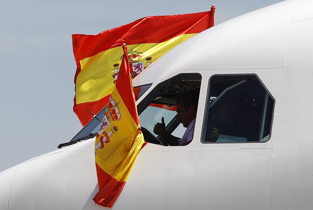 The plane's captain gives a thumbs up and flies Spanish flags, after landing with the Spanish soccer team aboard at Madrid's Barajas airport with the World Cup trophy (2010)