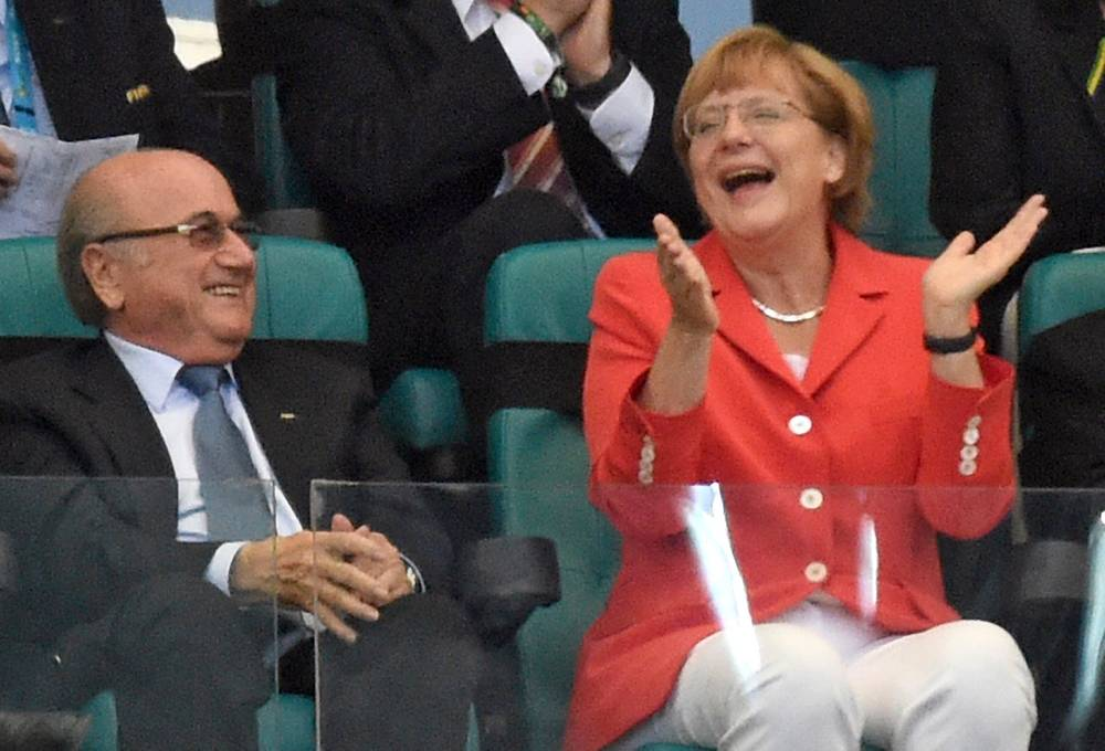 German Chancellor Angela Merkel (R) celebrates Germany's goal next to FIFA President Sepp Blatter during the FIFA World Cup 2014 group G preliminary round match between Germany and Portugal