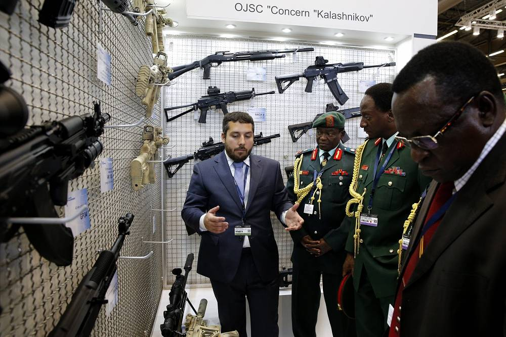 A Kalashnikov commercial attendant (L) presents the products to Tanzania military officers