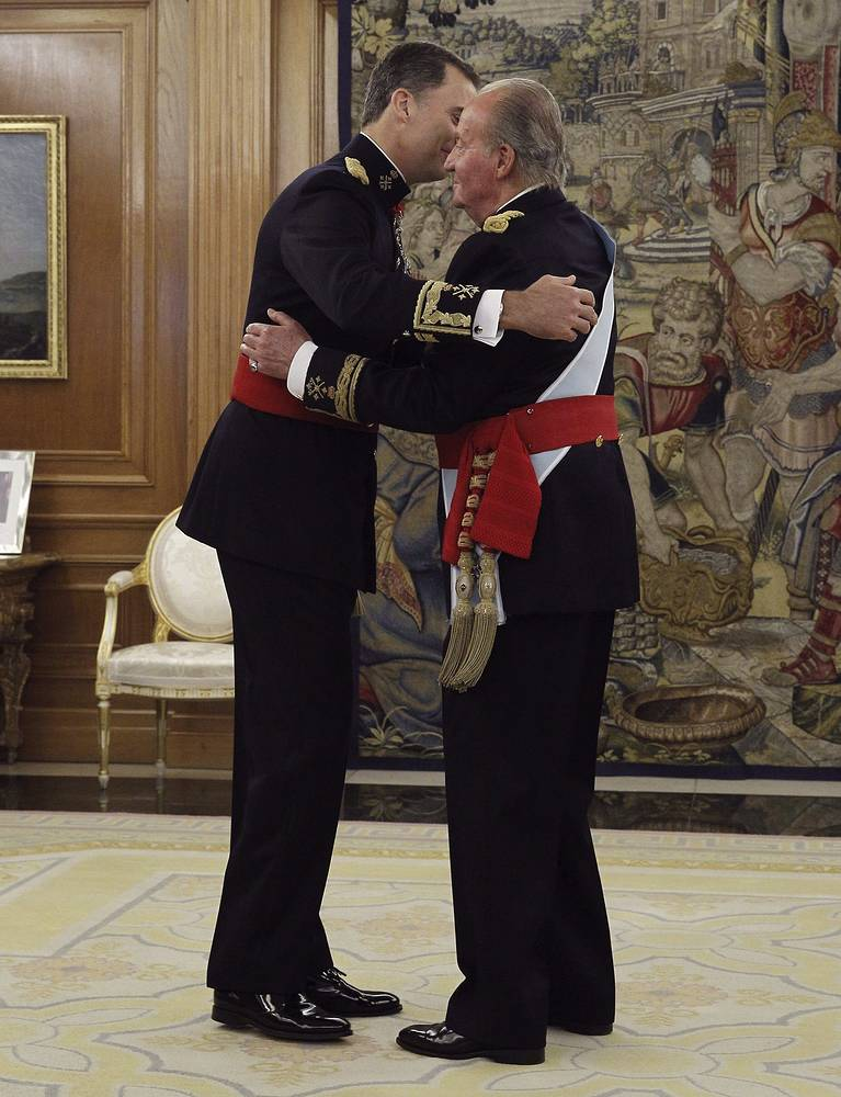 King Juan Carlos (R) embraces his son, the new King of Spain Felipe VI