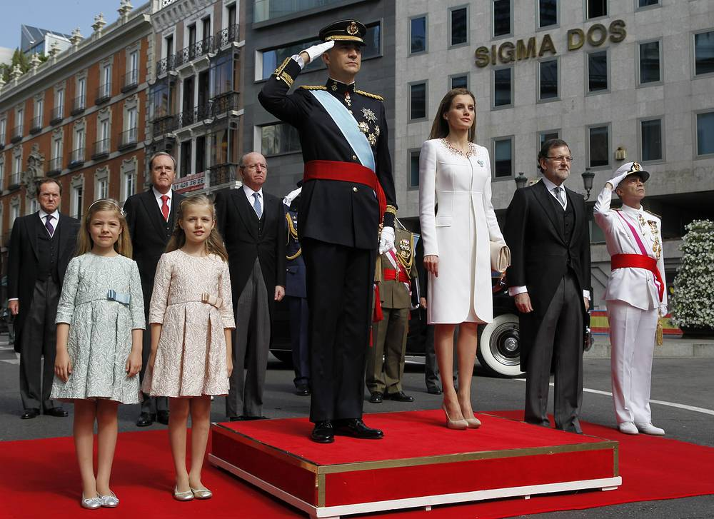 Spanish new King Felipe VI, Queen Letizia, their daughters, Princess Leonor of Asturias (2-L) and Princess Sofia (L) and Spanish Prime Minister Mariano Rajoy (2-R) stand at the national anthem