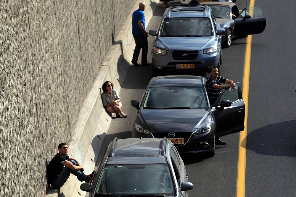 People take cover near their cars while sirens sound over the city of Tel Aviv