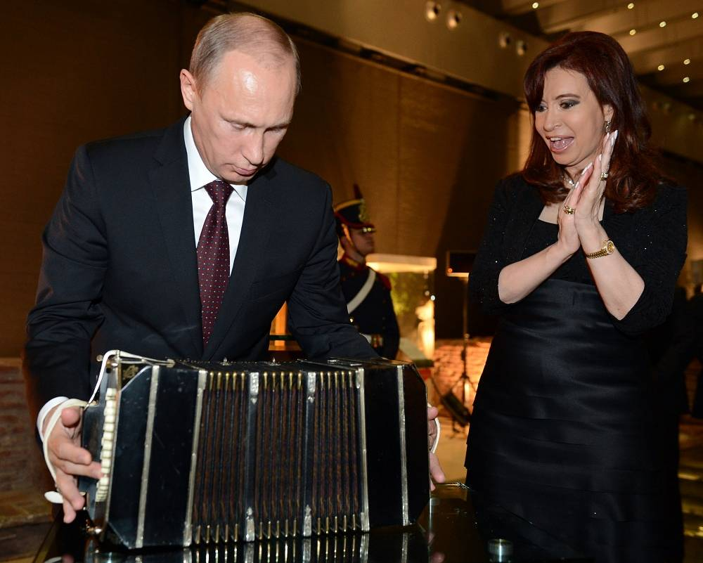 Vladimir Putin examines a bandoneon - a gift from Argentina's President Cristina Fernandez de Kirchner
