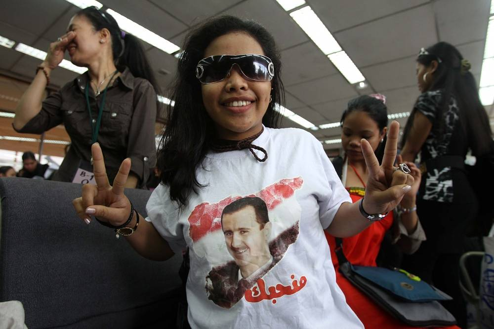 A Filipino wears a T-shirt with a portrait of Syrian President Bashar al-Assad