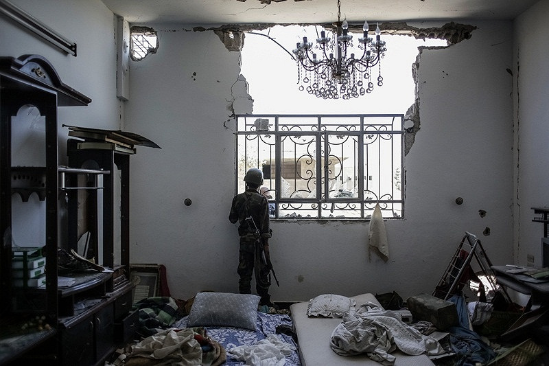 A soldier of Syrian government forces in a house seized from the militants during battle near Damascus, Syria, 2013