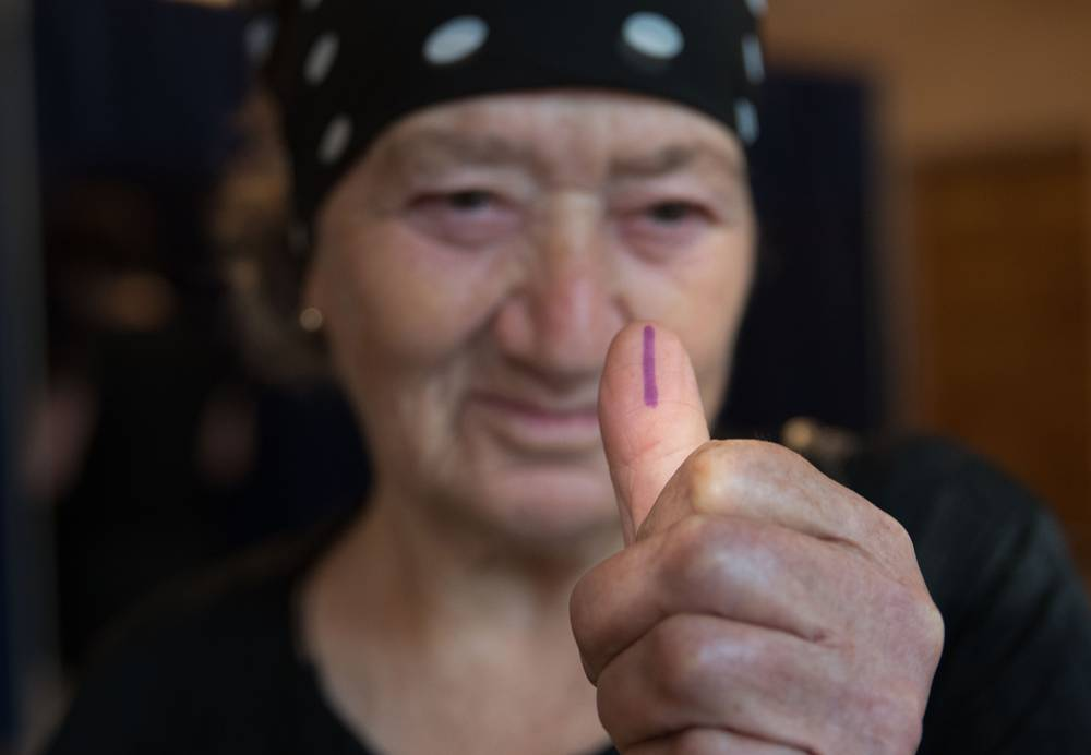 A woman shows a marked finger after voting