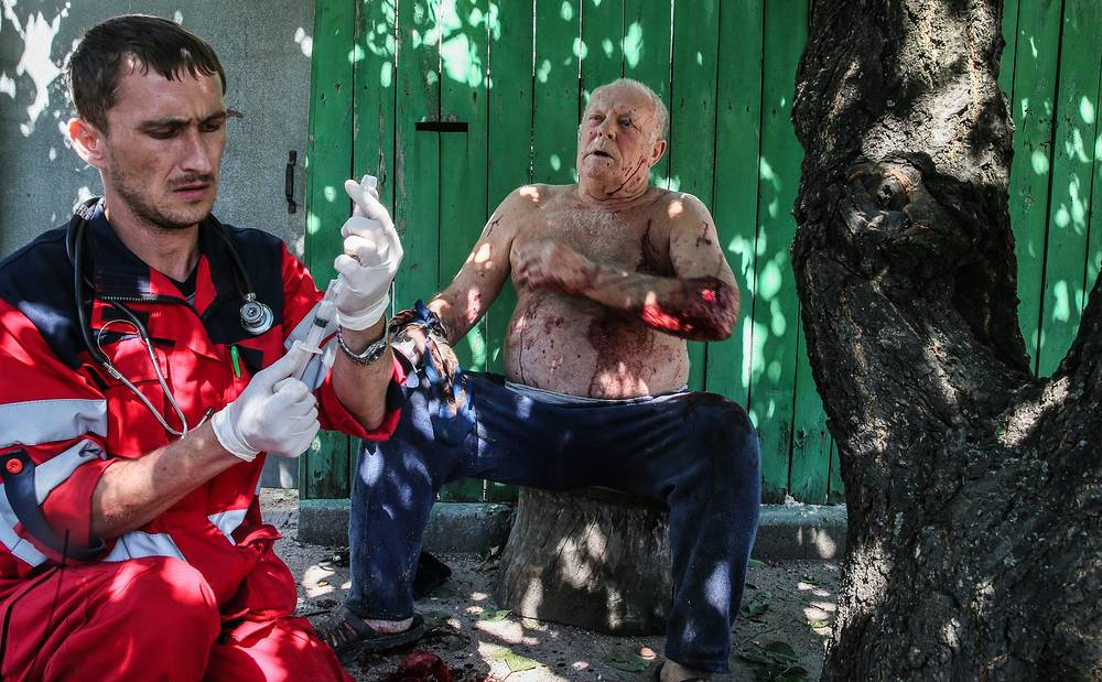 A paramedic helps a man wounded in a shelling attack on Donetsk