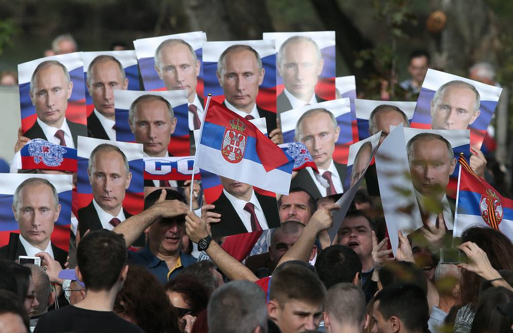 Photo: People hold portraits of Vladimir Putin at a military parade in Belgrade, 16 October 2014