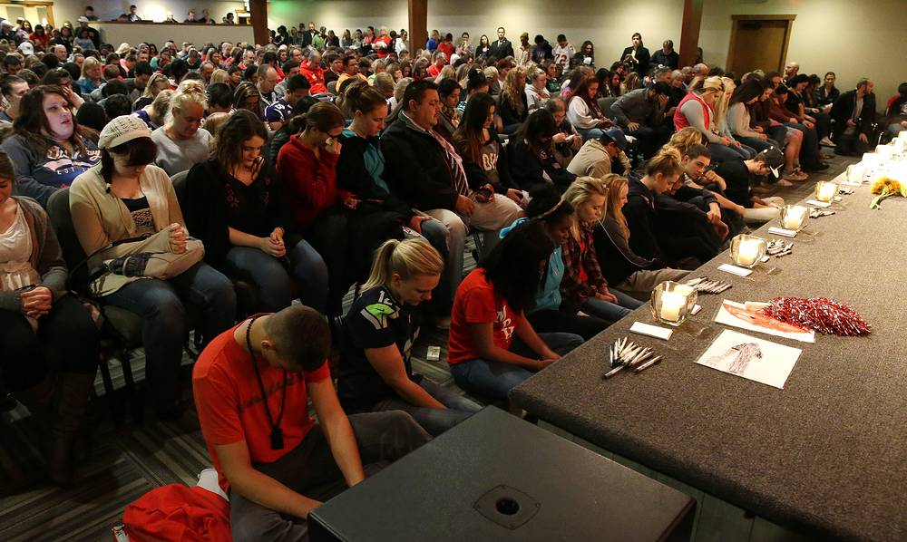 Young people bow their heads during a memorial vigil at the Grove Church in Marysville, Washington, October 24, 2014