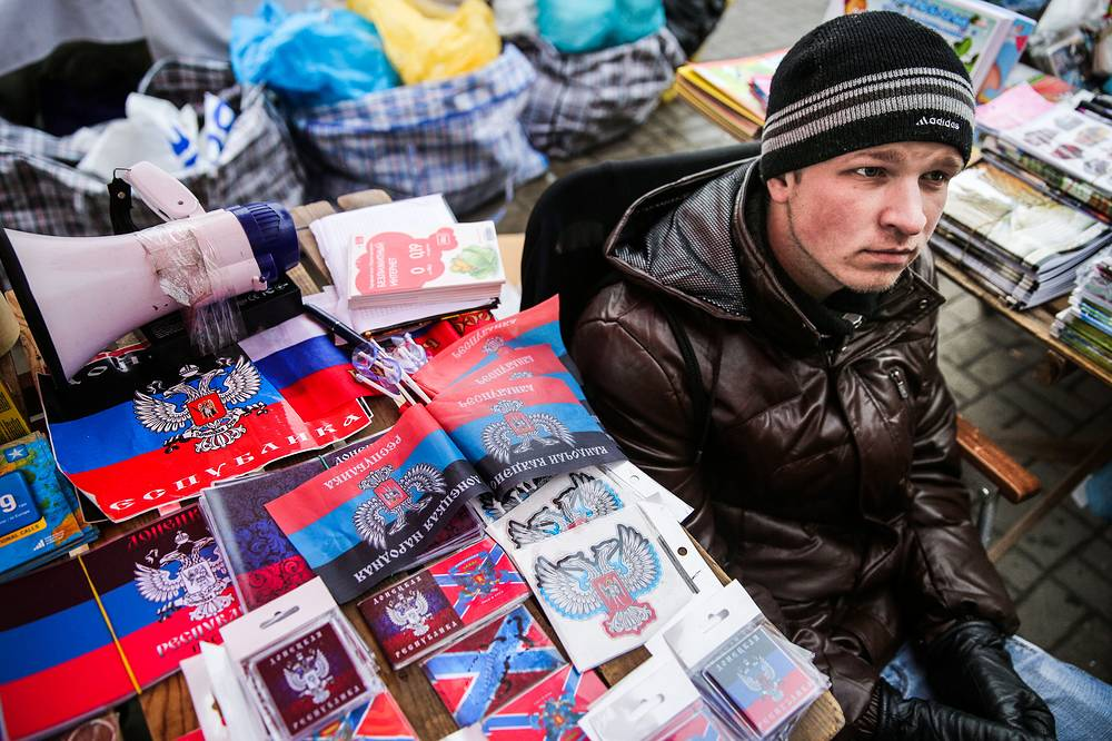 The parties to the Ukrainian conflict agreed on a ceasefire at OSCE-mediated talks on September 5 in Belarusian capital Minsk. Photo: A man selling flags and badges bearing the coat of arms of self-proclaimed Donetsk People's Republic in Donetsk