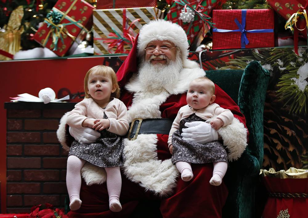 Photo: A man portraying Santa Claus poses with children at the Maine Mall in South Portland, US