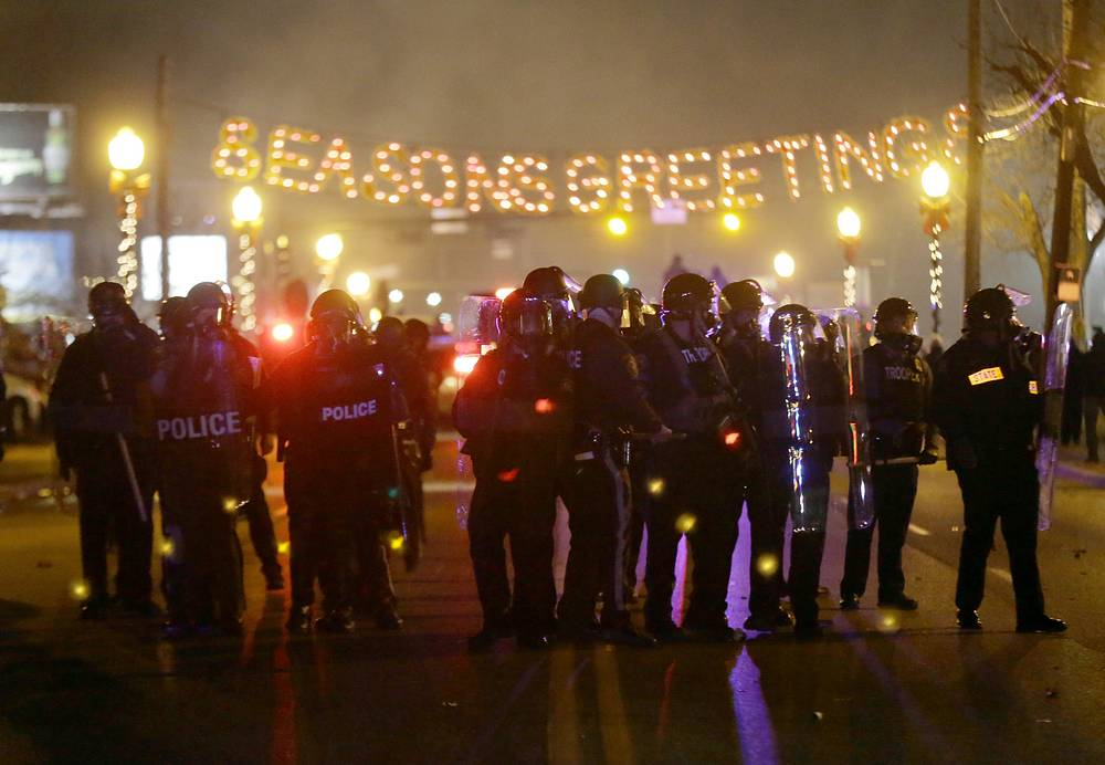 The death of the 18-year-old Michael Brown in early August sparked several weeks of riots in the St. Louis suburb and exposed racial tensions that have been building up for years. Photo: Police gather on the street as protesters react after the announcement of the grand jury decision, November 24, 2014, in Ferguson, US