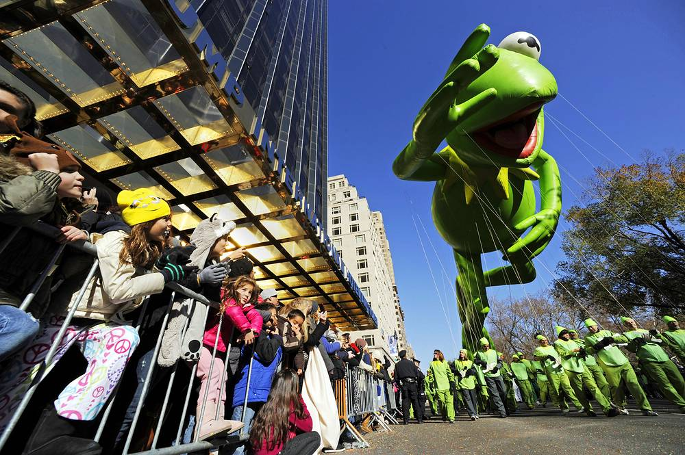 Children watch the Kermit the Frog balloon pass by at Macy's 85th Annual Thanksgiving Day Parade in New York City in 2011