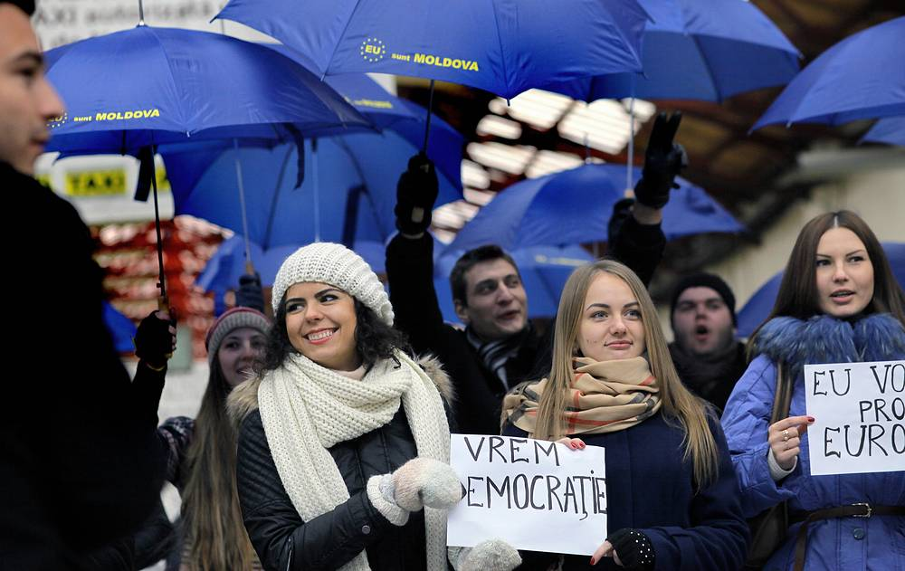 As many say, these parliamentary elections will decide the country's future foreign policy course. Photo: Moldovan students display EU colored umbrellas and placards before to go polling for Moldova's parliamentary elections in Bucharest, Romania