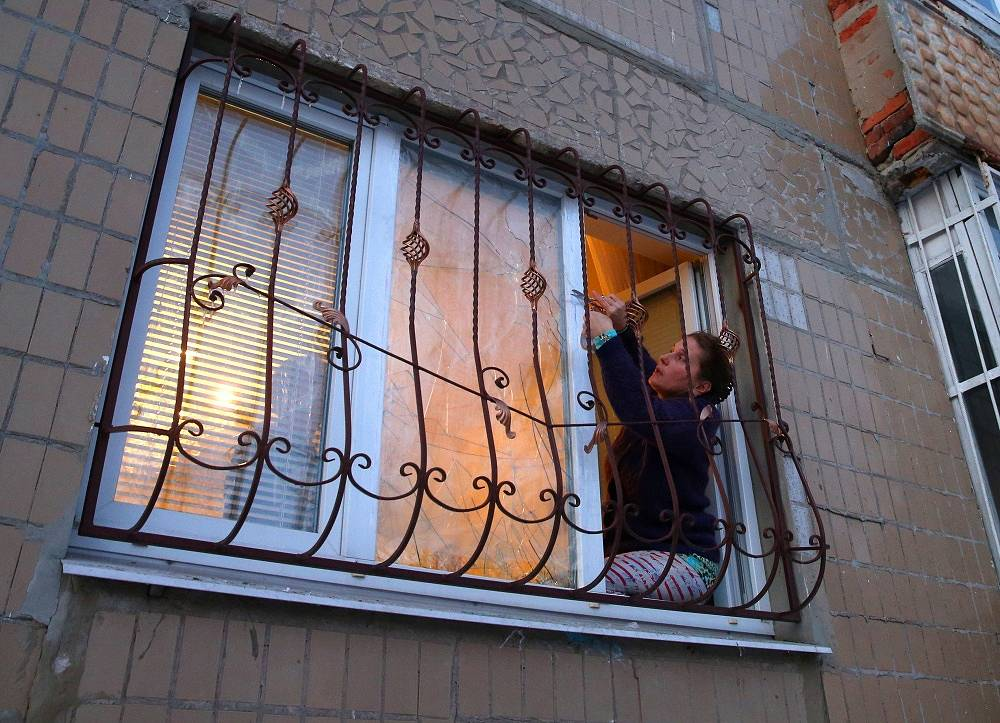 Photo: Donetsk resident tapes a broken window in his apartment after a shelling attack