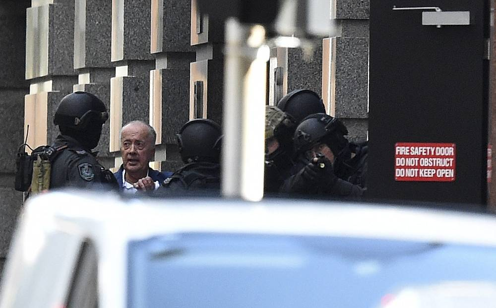 Photo: A released hostage speaks with police near a Lindt Cafe, Sydney, 15 December 2014