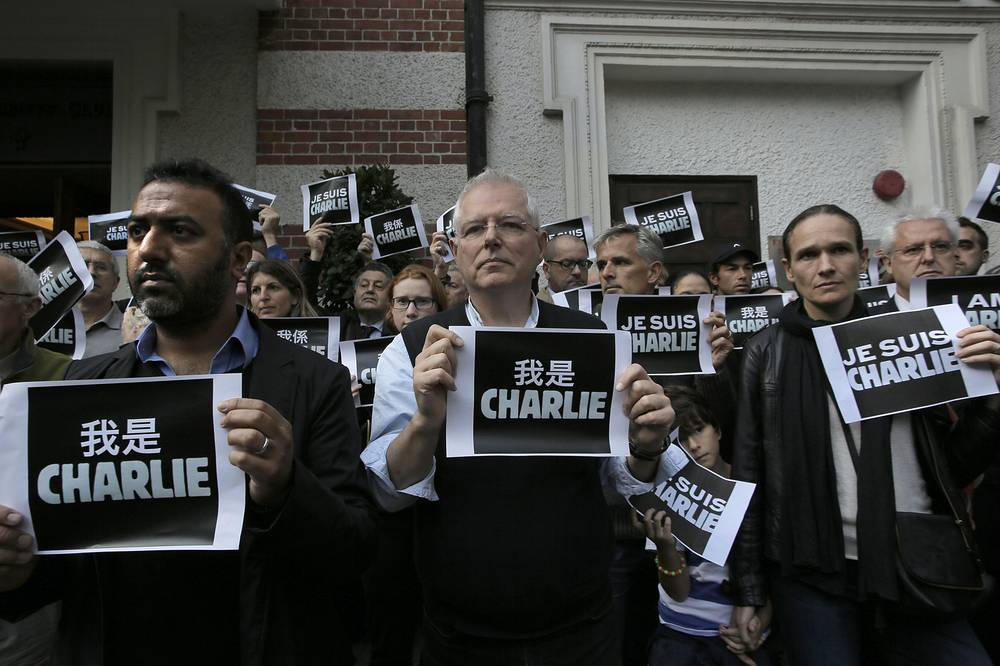 "Journalists and supporters of press freedom show off signs ""Je Suis Charlie (I Am Charlie)"" outside The Foreign Correspondents' Club in Hong Kong"