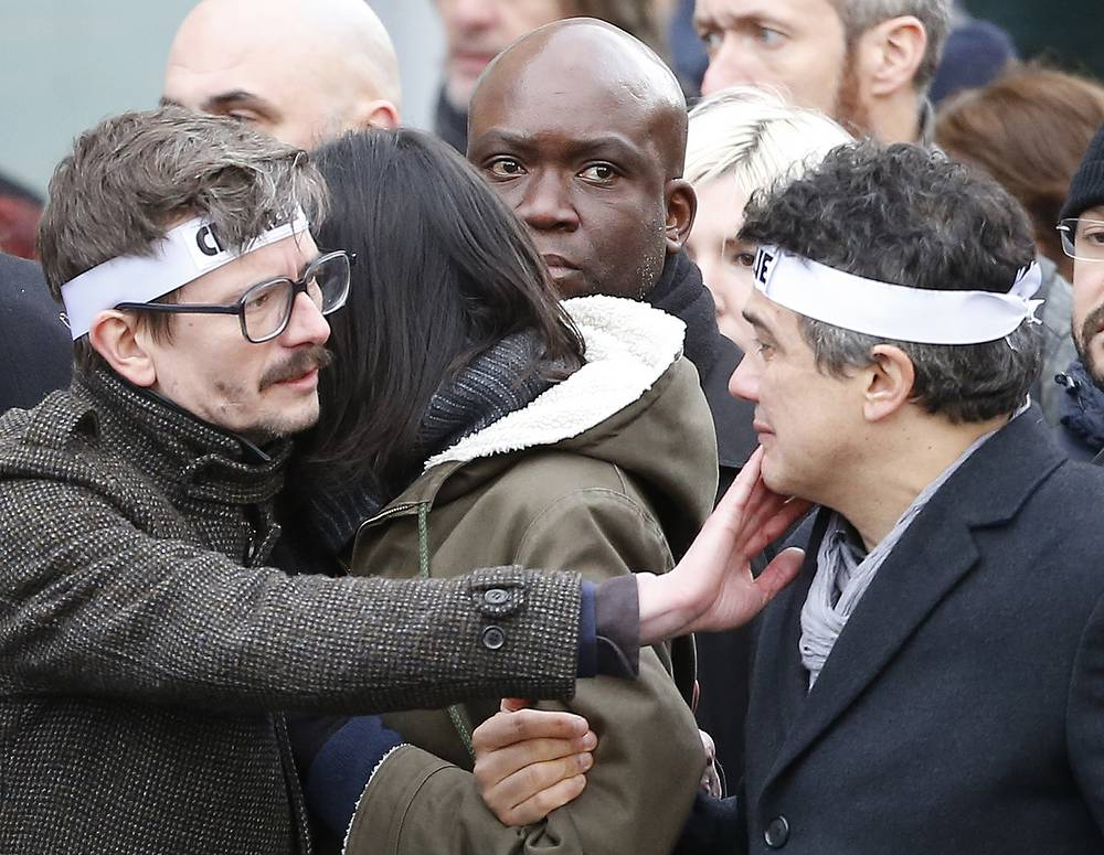 Photo: Charlie Hebdo newspaper staff, with editorialist Patrick Pelloux, right, cartoonist Renald Luzier, left, during march in Paris on January 11, 2015