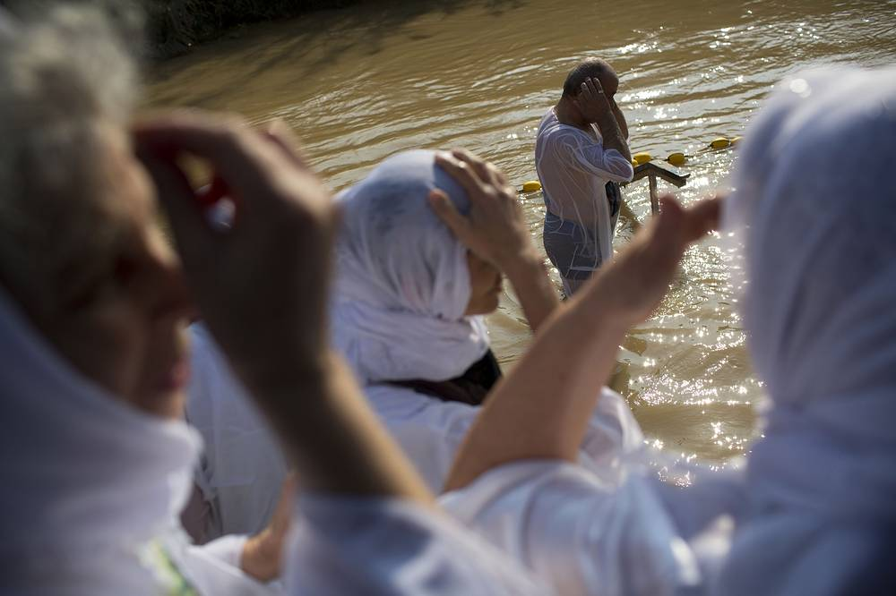 Christian Orthodox pilgrims bathe in the Jordan river during a baptism ceremony at Qasr-el Yahud near the West Bank town of Jericho