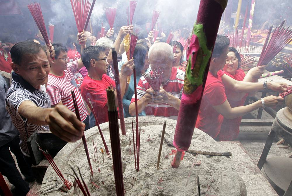 Indonesian ethnic Chinese light incense sticks as they pray during the Chinese New Year celebrations at the Dharma Bhakti temple in Jakarta, Indonesia