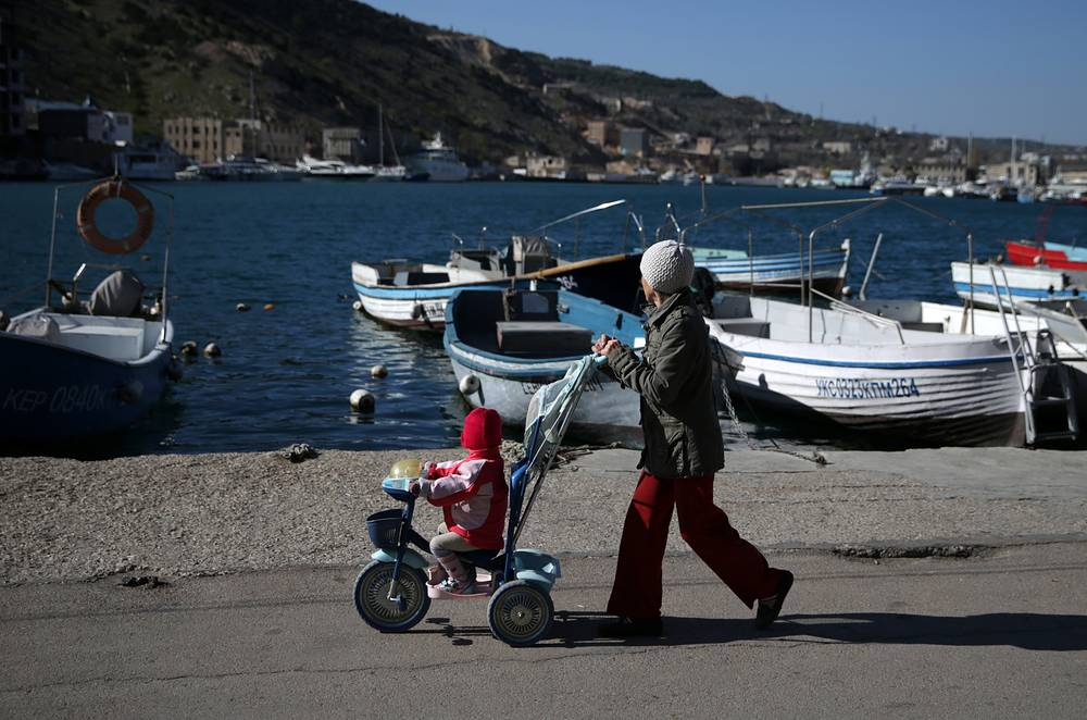 Ruble became the monetary unit of the peninsula after the signing of the federal law on Crimea's reunification with Russia. Photo: Woman with a child Balaklava Inlet, Sevastopol