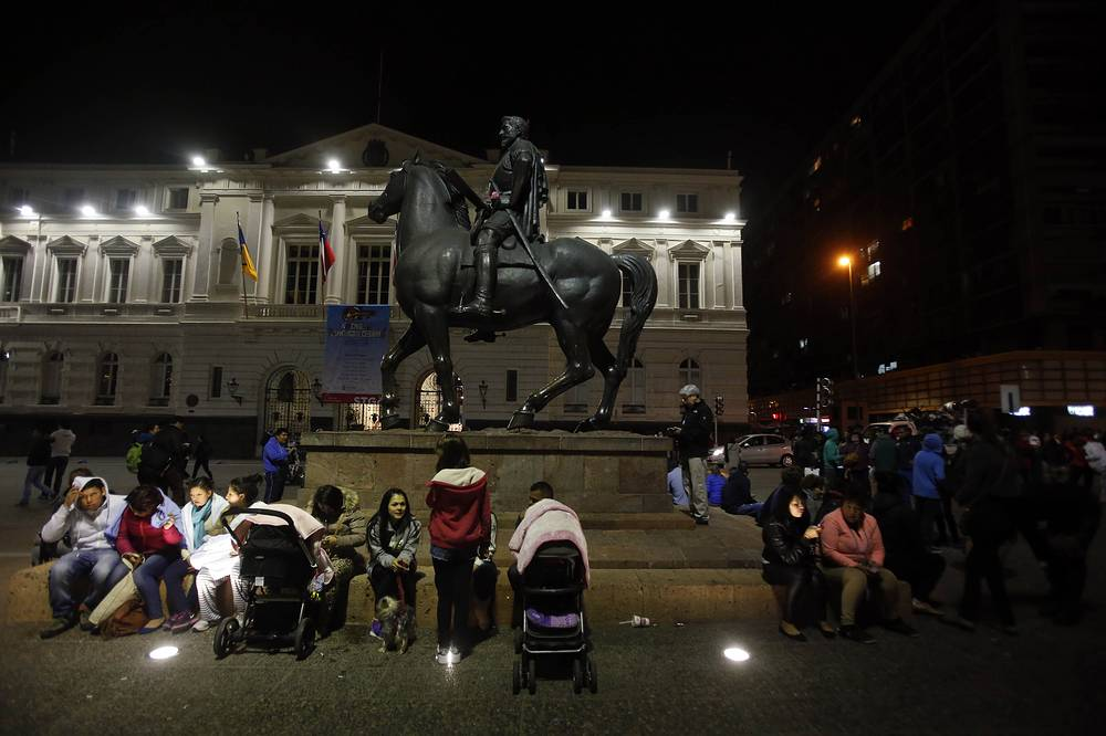 Residents sitting next to an equestrian statue, in Santiago's main square after the earthquake
