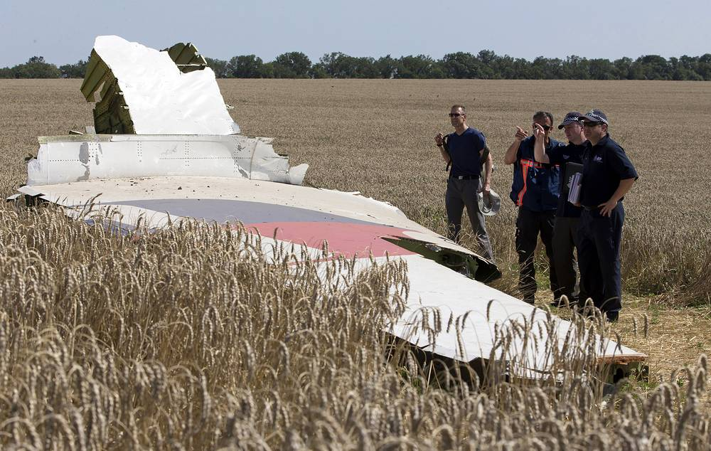 Two parallel investigations, into the cause of the crash and a criminal inquiry, were initiated by the Dutch side. Photo: Investigators examining a piece of the Malaysia Airlines Flight 17 plane crash near the village of Hrabove, Donetsk region, eastern Ukraine