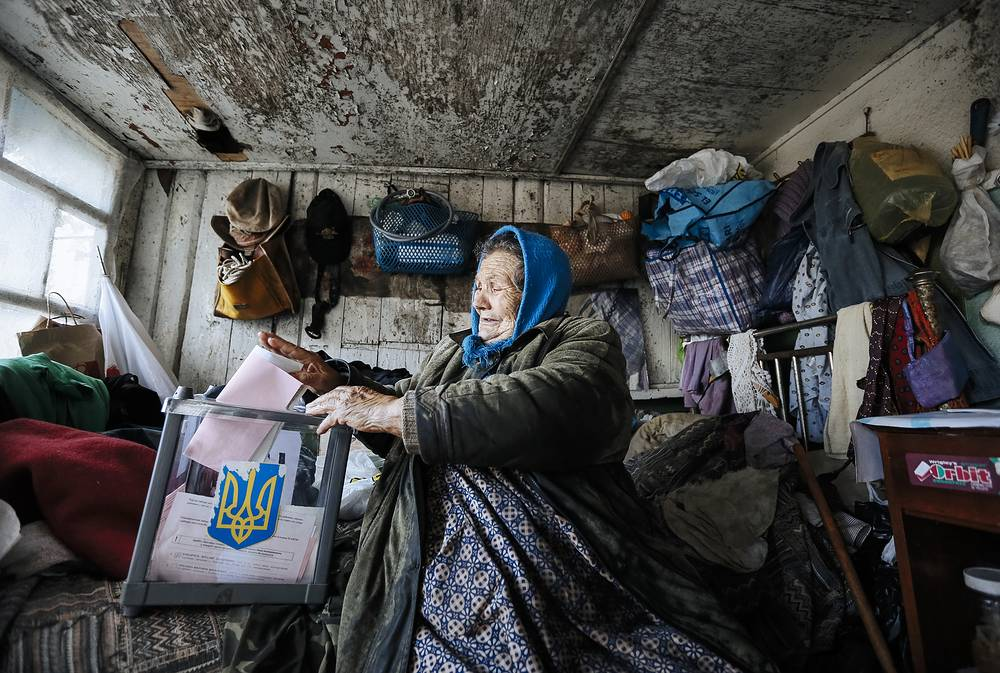 An elderly woman at a mobile polling station during Ukrainian local elections in Podgortsi village, near Kiev