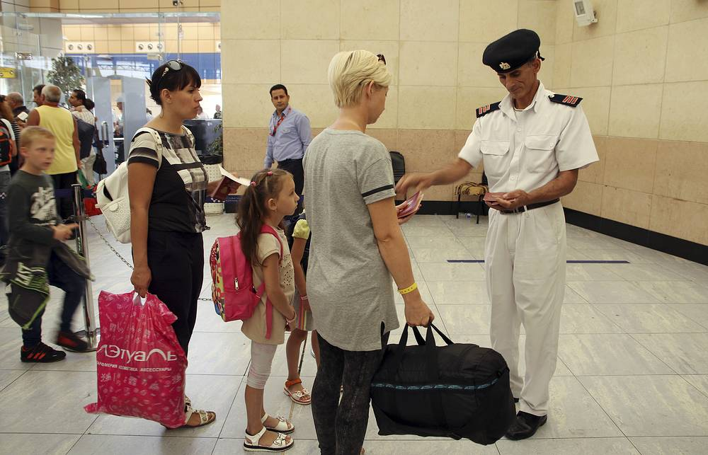 Tourists have their documents checked by Egyptian police as they prepare to be evacuated from Sharm el-Sheikh airport, Egypt