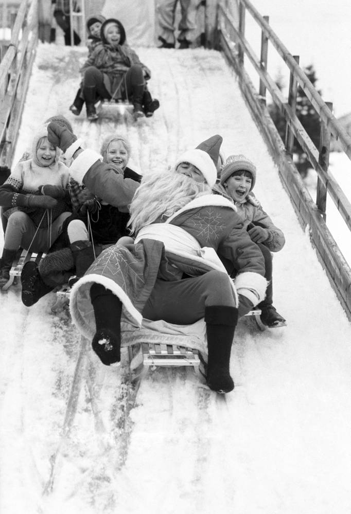 Grandfather Frost sledding with children in a winter camp, Moscow region, 1984