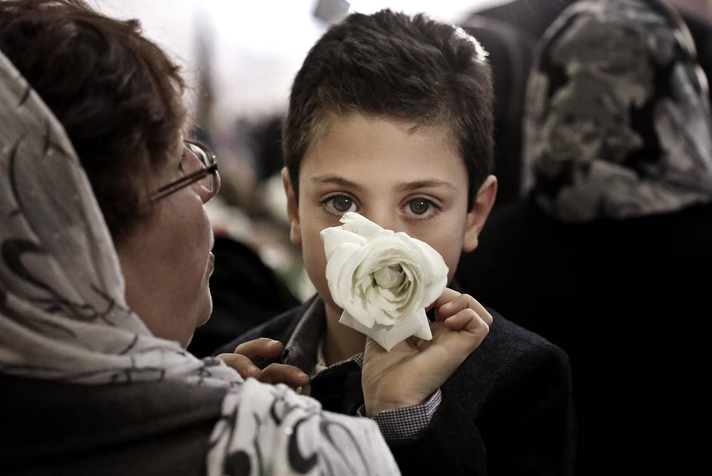 A boy with a flower at Christmas Eve Mass, St. Mark's Cathedral, in Cairo, Egypt